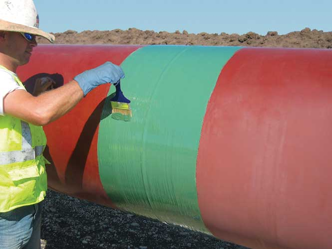 Worker applying a protective coating to an exposed pipeline